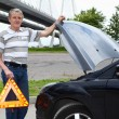 Mature man holding emergency triangle and opened car hood — Stock Photo #12200273