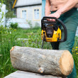 Caucasian senior male trying to start chainsaw for cutting the log - Stock Photo