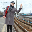 Woman in coat and cap with red bag wave goodbye standing on train station - Stock Photo
