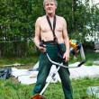 Mature man a lawn-mower with chopper trimer mowing grass. — Foto de Stock