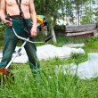 Stock Photo: Unrecognizable person a lawn-mower with chopper trimer mowing grass. Focus on trimer