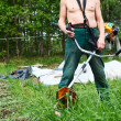 Unrecognizable man a lawn-mower with chopper trimer mowing grass. Focus on trimer — Stock Photo #12200297
