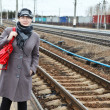 Portrait of happy fashion young Caucasian woman standing on railway station. Looking far away. Copy space — Stock Photo #12200304