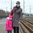 Mother and small daughter standing on railway station platform — Foto de Stock