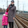 Mother and small daughter standing on railway station platform - Stock Photo