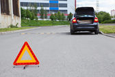 Triangle warning sign on road foreground and broken car with blinker lights on road wayside — Stock Photo