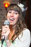 Szczęśliwy atrakcyjną kobietę jako wokalista trzyma mikrofon — Zdjęcie stockowe
