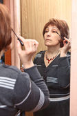 Mature Caucasian woman applying make-up against mirror in domestic room — Stock Photo