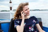 Speaking on mobile phone woman in dress at ship cafe — Stock Photo