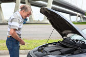 Confused mature driver standing in front of vehicle with opened engine compartment hood — Stock Photo