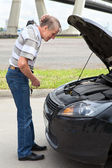 Confused mature driver standing in front of car with opened engine compartment hood — Stock Photo