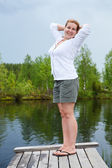 Morning exercises near lake on planked footway — Stock Photo