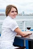 À la recherche de femme dos avec verre de vin rouge, assis à la table de café — Photo