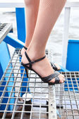Beauty female legs in fishnet tights and shoes in high heels standing on stairs — Stock Photo