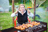 Hungry young female with fork and knife in hands sitting and waiting for grill meat — Stock Photo