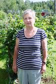 Senior kaukasisk kvinna som står i grönskande trädgård — Stockfoto