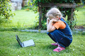 Little interested girl watching dvd movies on device in green lawn — Stock Photo