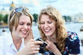 Two cheerful beauty women looking at screen of simple hand-held camera — Stock Photo