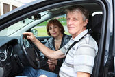 Senior Caucasian male and woman sitting in land vehicle and smiling — Stock Photo