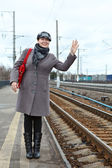 Woman in coat and cap with red bag wave goodbye standing on train station — Stock Photo