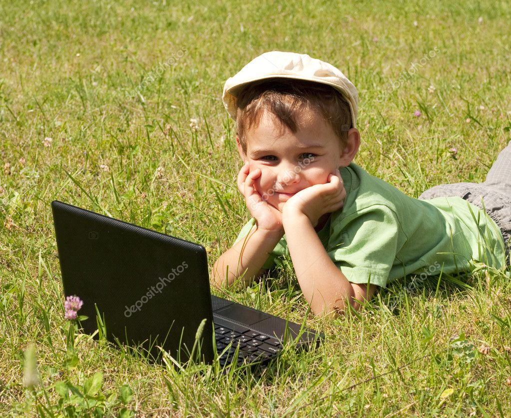 Kid with laptop on green meadow — Stock Photo #12223109