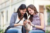 Due belle donne, invio di messaggi con mobile — Foto Stock