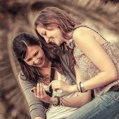 Dos hermosas mujeres enviando mensajes con el móvil — Foto de Stock