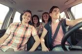 Czterech przyjaciół w samochodzie, pozostawiając na wakacje — Zdjęcie stockowe