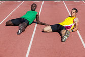 Two Track and Field Athletes Stretching — Stock Photo