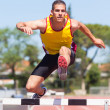 Male Track and Field Athlete during Obstacle Race - Stock Photo