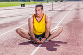 Track and Field Athlete Stretching — Stockfoto
