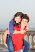 Smiling Young Couple Piggybacking — Stock Photo