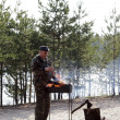 Man burning fire in grill — Stock Photo
