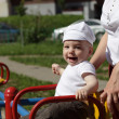 Happy baby on roundabout — Stock Photo