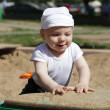 Stock Photo: Happy baby playing in sandbox