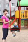 Mother holding swing — Stock Photo