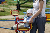 Mother pushing carousel with child — Stock Photo