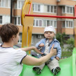 Serious child sitting on slide — Stock Photo