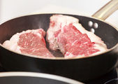 Beef steak in a frying pan — Stock Photo