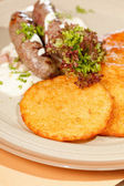 Potato pancakes with sausages — Stock Photo