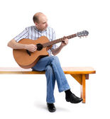Handsome young man playing guitar, sitting on a bench — Stock Photo