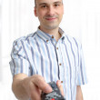 Young man with a TV remote — Stock Photo