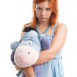 Young woman hugging big burro toy - Stock Photo