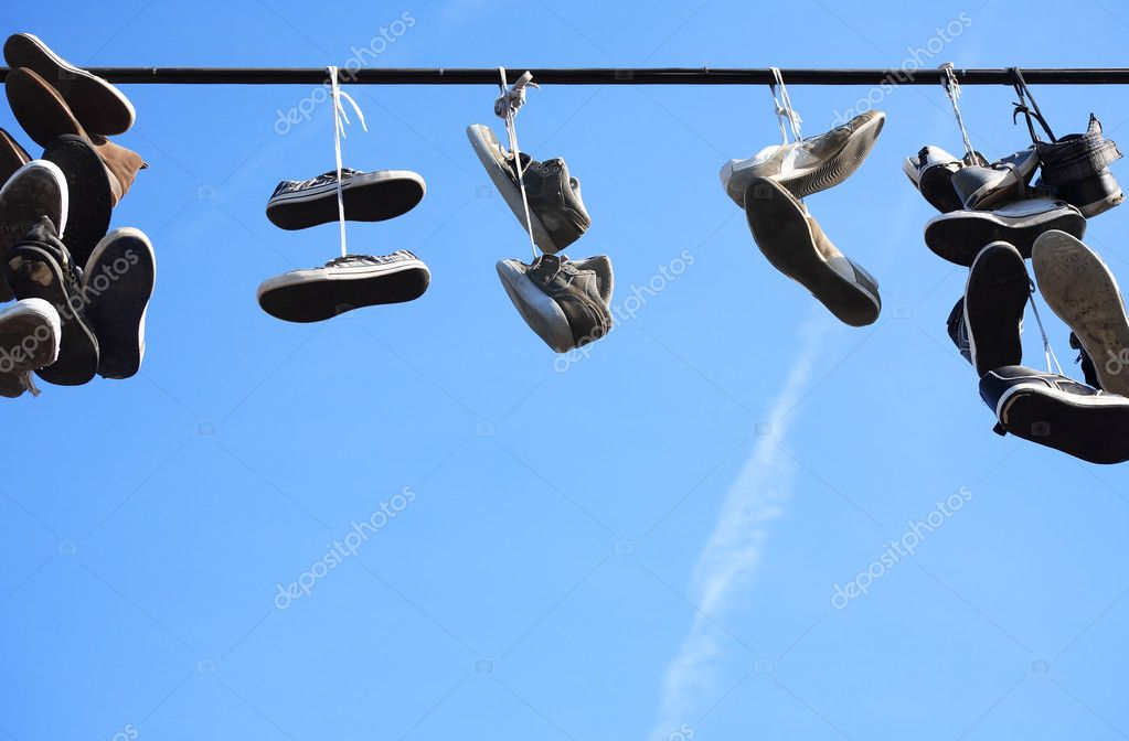 Lot of worn shoes hanging on wire against blue sky  Stock Photo #12004683