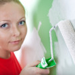 Woman with paint roller in hand — Stock Photo