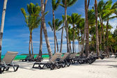 Chaise-longues on caribbean sea beach — Stock Photo