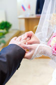 Bride putting a ring on groom's finger — Stock Photo