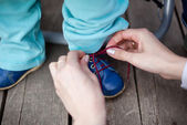 Mother care - tying a shoe — Stock Photo