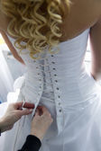 Helping the bride with bride's white corset — Stock Photo