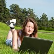 Girl in park lies on grass and work with laptop. — Stock Photo